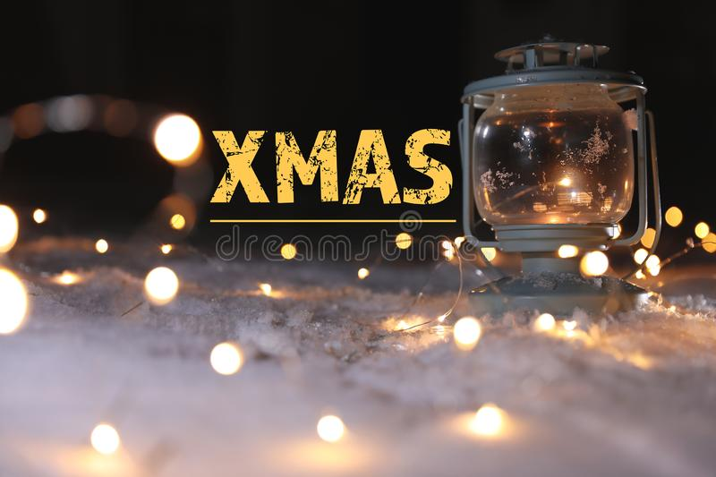 Burning lantern with Christmas lights on snow and message XMAS against dark background. Winter holidays royalty free stock photography