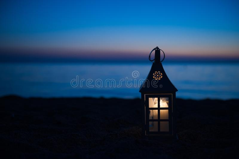 Burning lantern near the beach, sunset lighting. Lantern on a wooden deck near the beach at sunset royalty free stock images