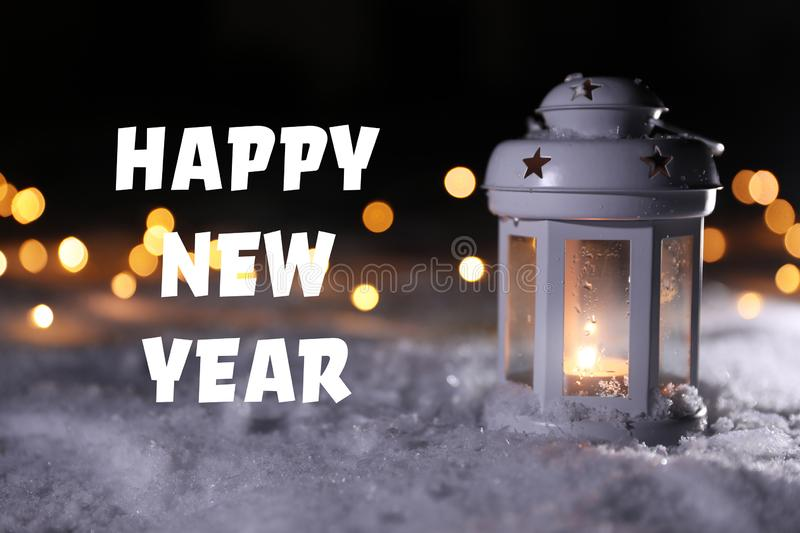 Burning lantern on snow and message HAPPY NEW YEAR against blurred background. royalty free illustration