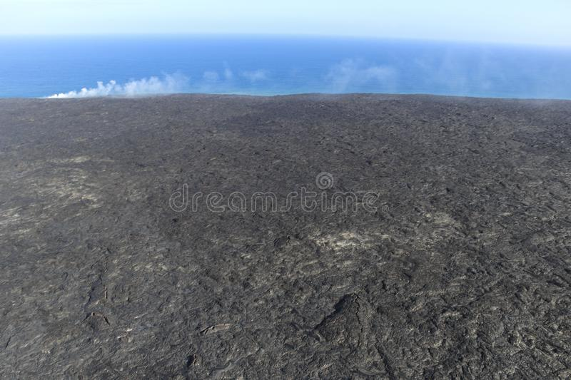 Helicopter aerial view of lava entering the ocean and steam, Big Island, Hawaii. royalty free stock photo