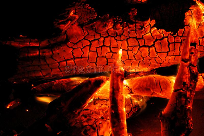 Burning log of wood close-up as abstract background. The hot embers of burning wood log fire. Firewood burning on grill royalty free stock image
