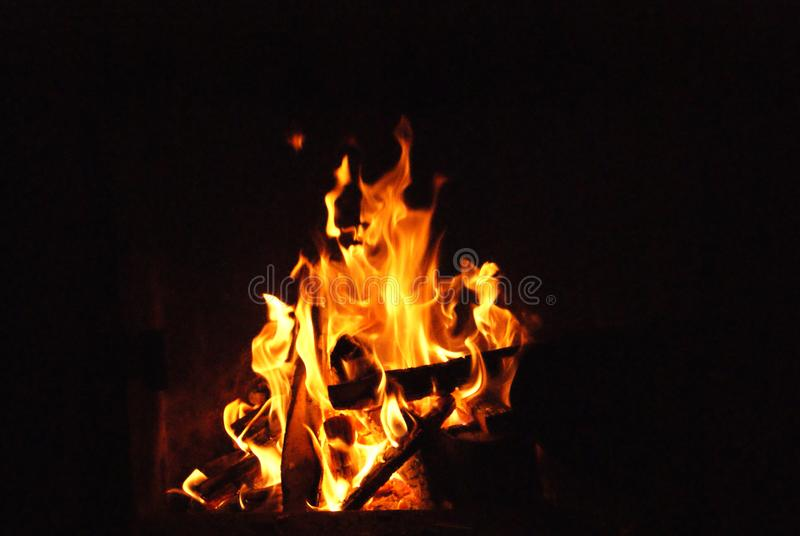 Burning logs bright fire dark night. Burning logs on an outdoor fire. Taken on a dark night the orange flames provide a beautiful contrast against the black royalty free stock image
