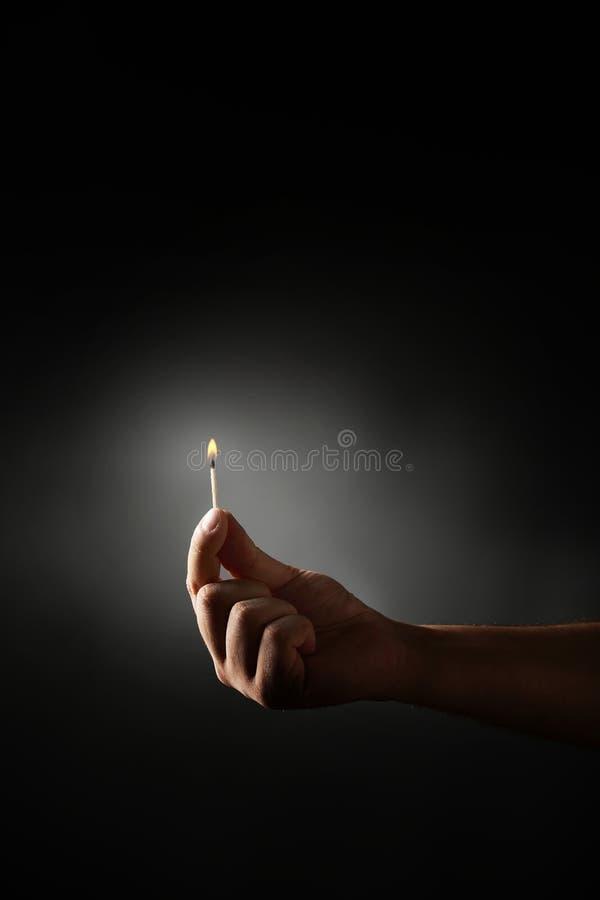 Burning match. Hand holding burning match against dark background royalty free stock image