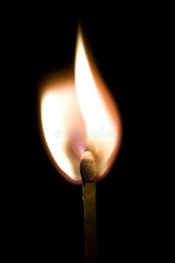 Burning Match. Burning wooden match on black background stock images