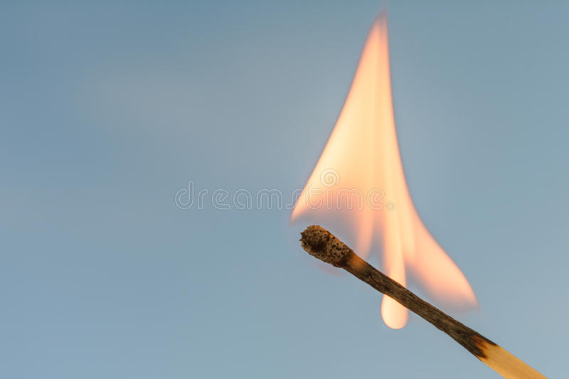 Burning match on a blue background royalty free stock images