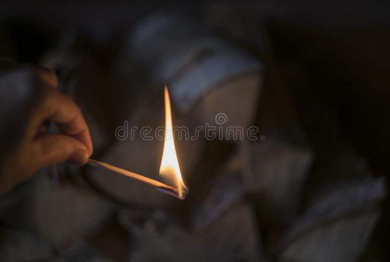 Burning match in the hand at blurred firewood background, fire country style and village photo. Cozy warm mood stock images