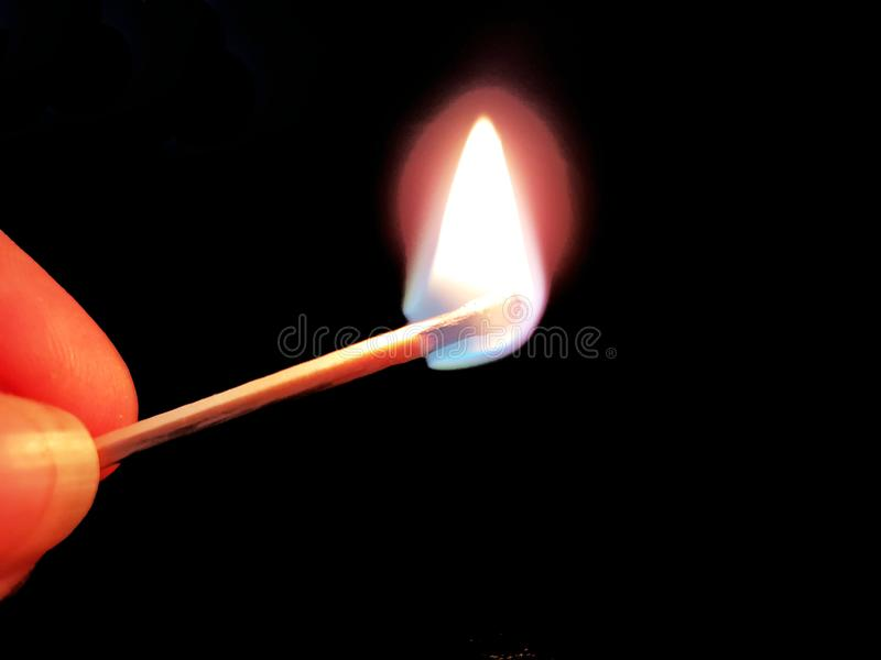 Burning match in hand on neutral background. Burning match in hand on neutral dark background royalty free stock image