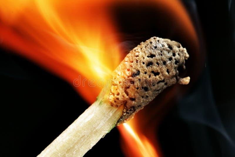 Burning match macro. Burning match close-up over black background stock image
