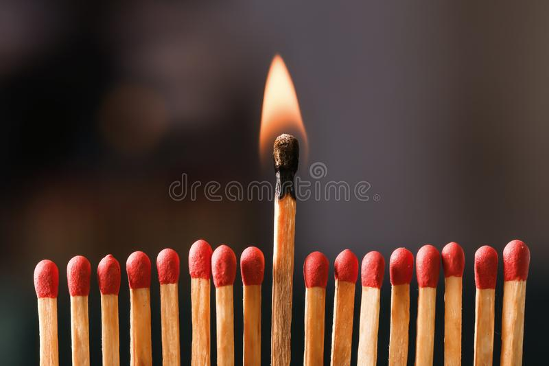 Burning match among others on black background royalty free stock photos