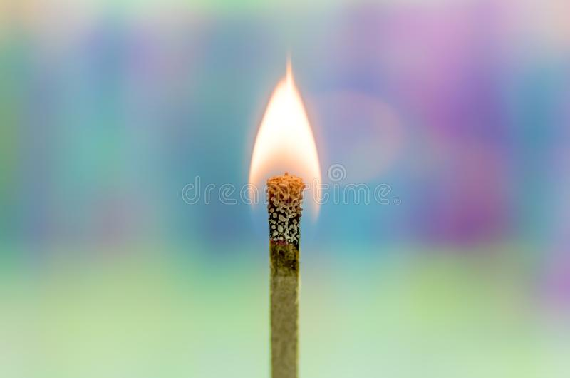 Burning Match with Rainbow Background. A match flame burns brightly against a soft, colorful rainbow holographic background stock image