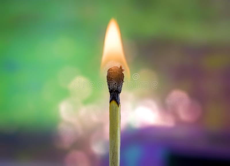 Burning Match with Rainbow Background. A wooden match flame burns brightly against a soft, colorful rainbow holographic background royalty free stock image