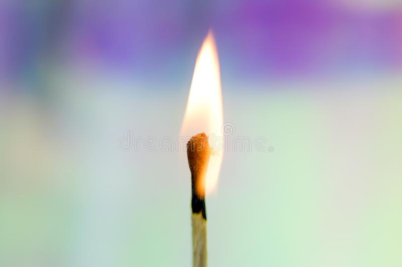Burning Match with Rainbow Background. A wooden match flame burns brightly against a soft, colorful rainbow holographic background stock images