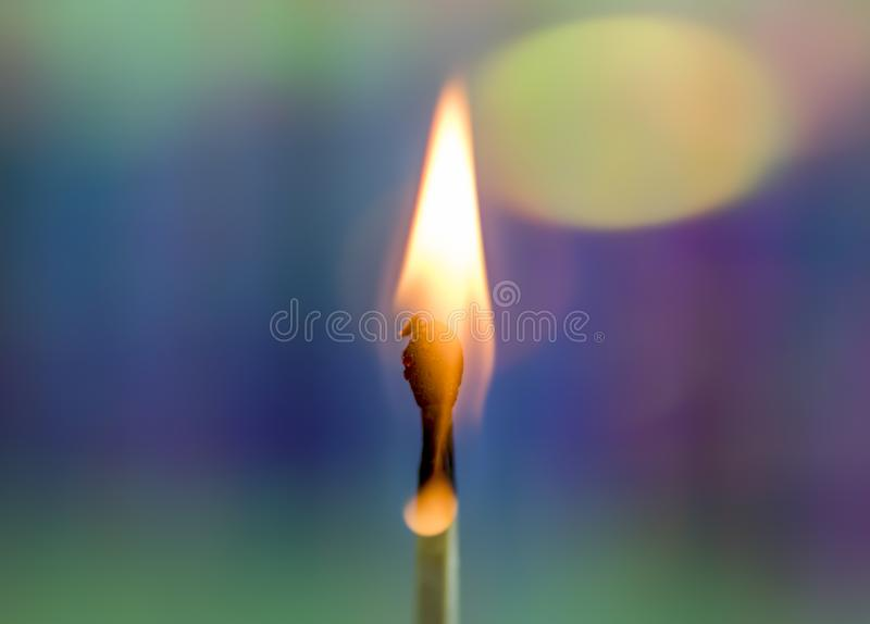 Burning Match with Rainbow Background. A wooden match flame burns brightly against a soft, colorful rainbow holographic background stock photos