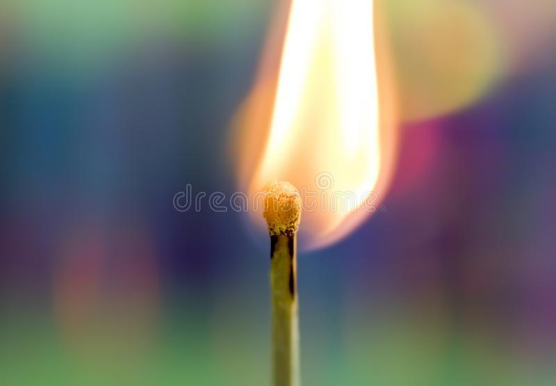 Burning Match with Rainbow Background. A wooden match flame burns brightly against a soft, colorful rainbow holographic background stock photo