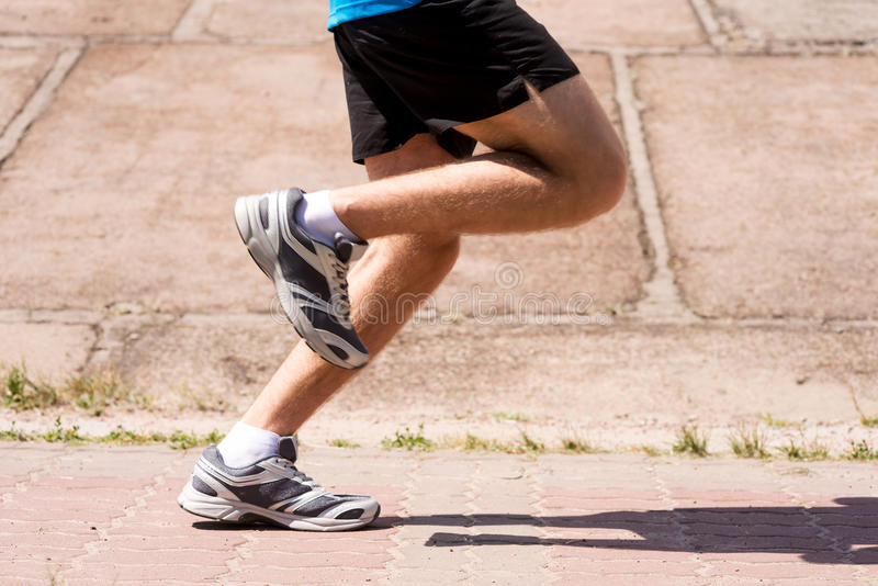 Burning the miles away. Side view close-up image of man running outdoors stock photo