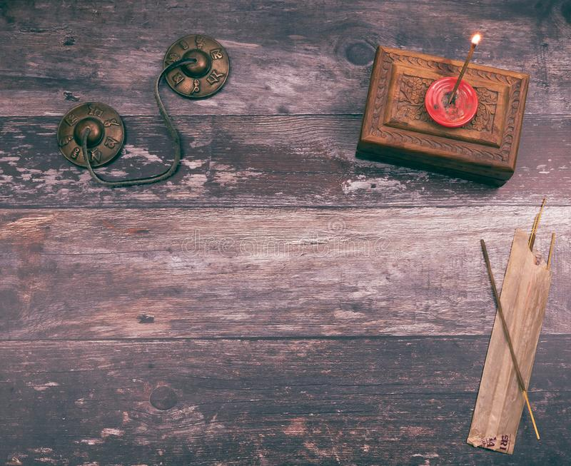 Burning a mystical incense stick in a mindfullness ritual to get a spiritual and peaceful meditation, with copyspace. On wood background stock photos
