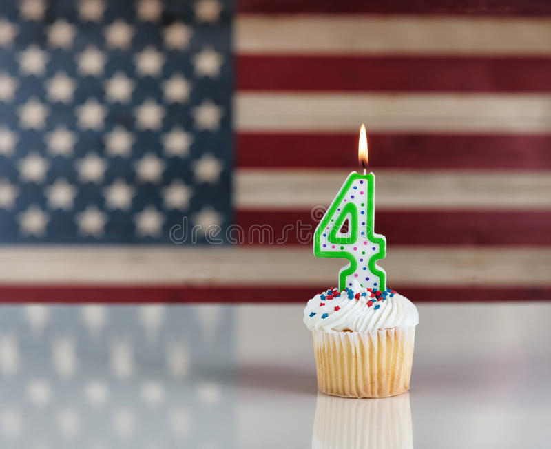 Burning number four candle inside cupcake with rustic wooden fla royalty free stock photos