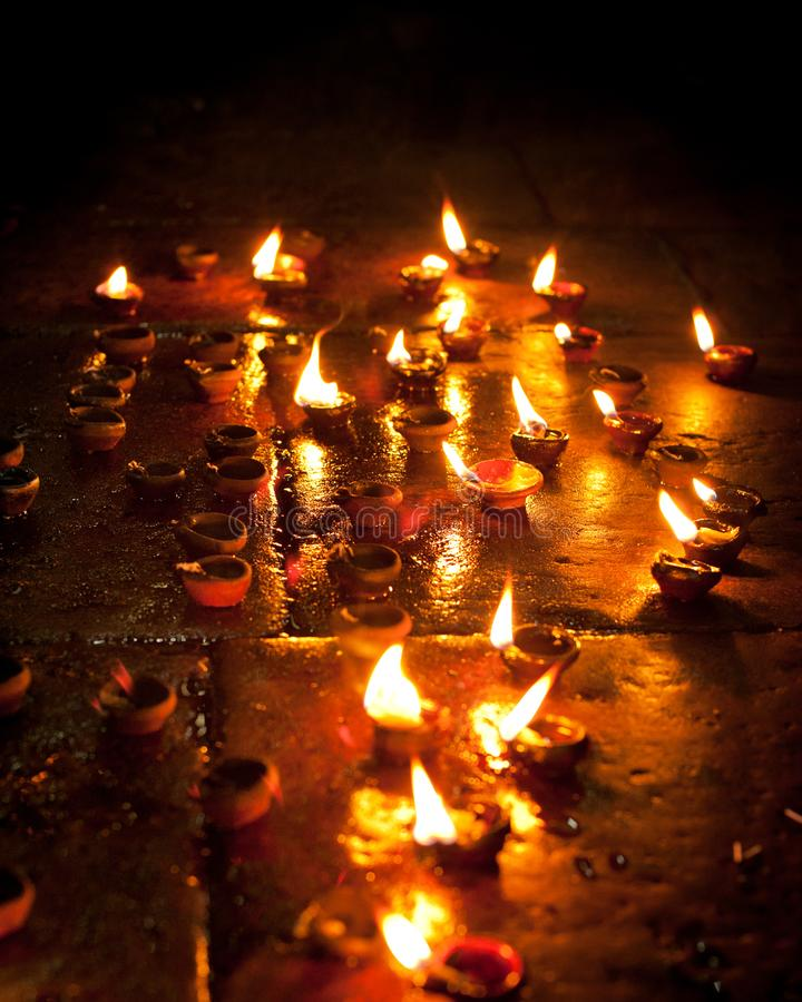 Burning oil lamps. Traditional offering in buddhist and Hindu temple. India. Burning oil lamps at religious ceremony. Traditional offering in buddhist and Hindu royalty free stock images