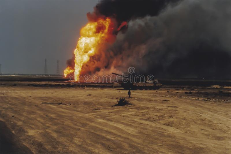 Oil well burning in field with remains of burned tank. Burning oil well in field coated in spilled oil in aftermath of Operation Desert Storm, Persian Gulf War royalty free stock images