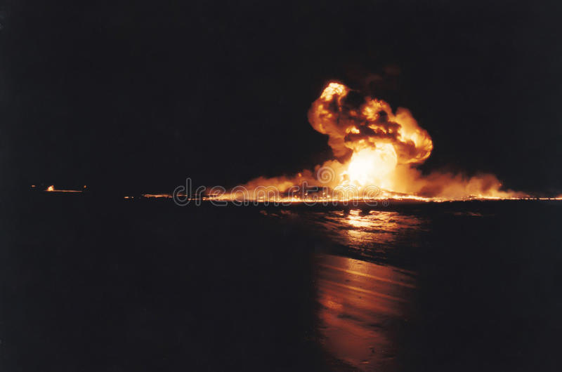 Burning oil well fire, Persian Gulf War, Kuwait. Kuwait City, Kuwait - April 1991 : Damaged burning oil well fire in daylight with skies darkened from smoke from royalty free stock photos