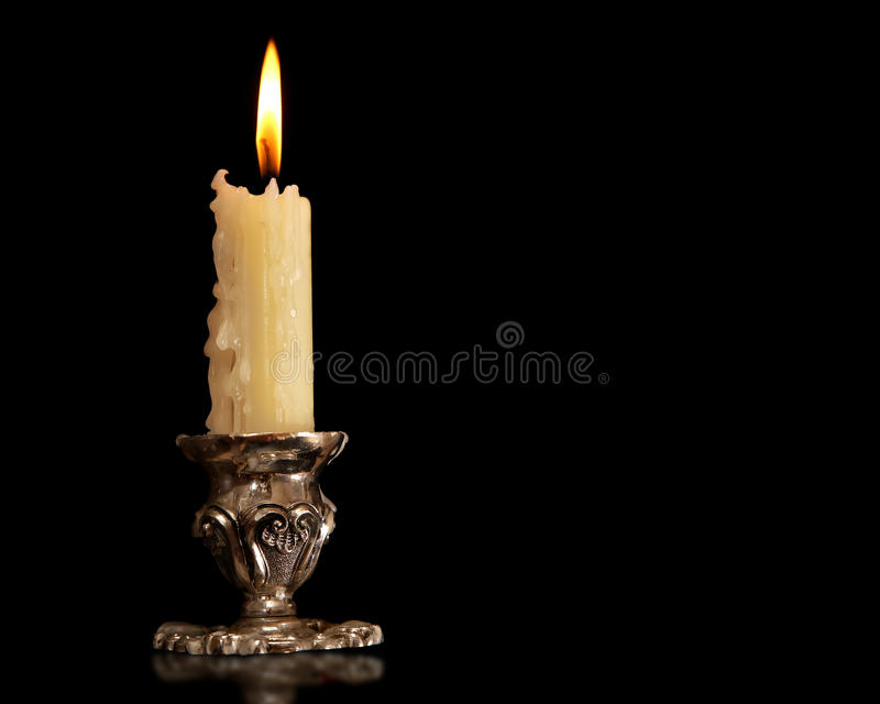 Burning old candle vintage Silver bronze candlestick. Isolated Black Background. royalty free stock photo