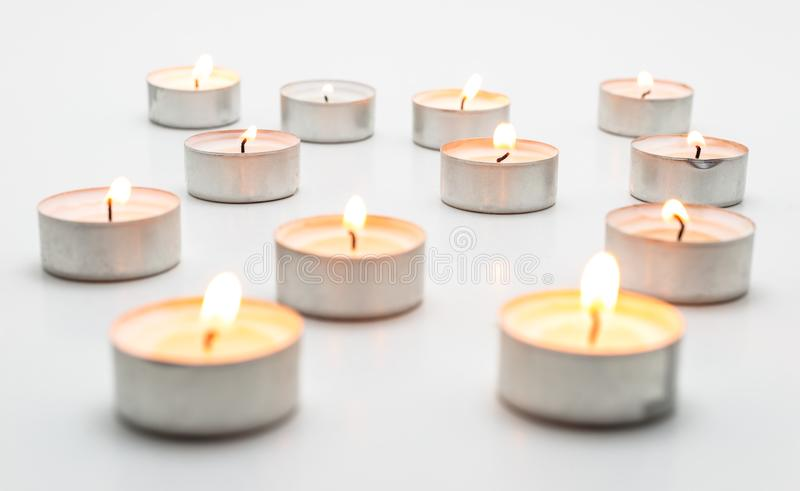 Burning paraffin candles, tealight, lies on a white background. Burning paraffin candles, tealight, lies on a white background royalty free stock photos