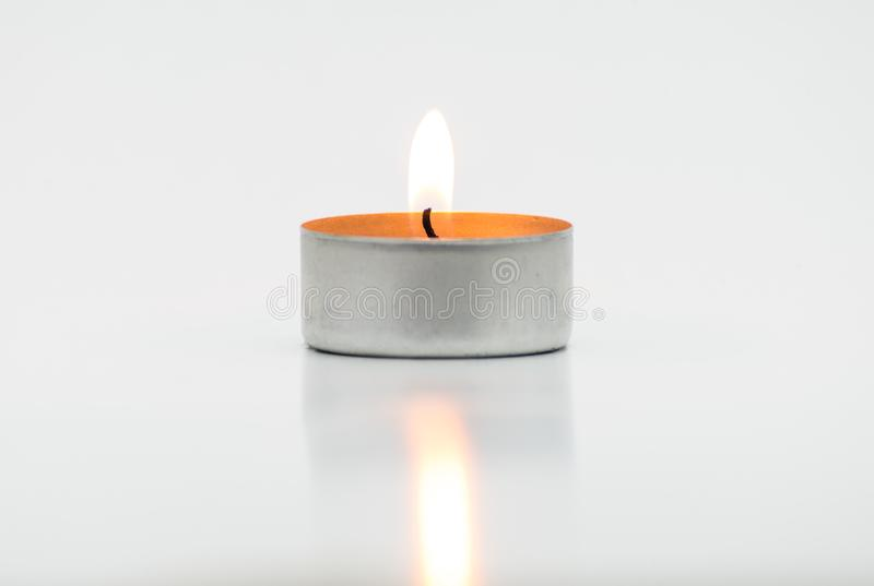 Burning paraffin candles, tealight, lies on a white background with a clipping path. Burning paraffin candles, tealight, lies on a white background with a stock images