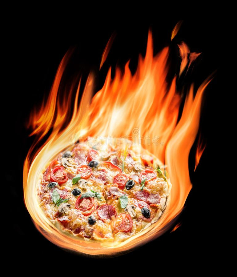 Burning pizza ingredients in flames on the black background.  stock photos