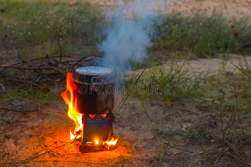 Burning portable wooden stove with a cauldron stock images