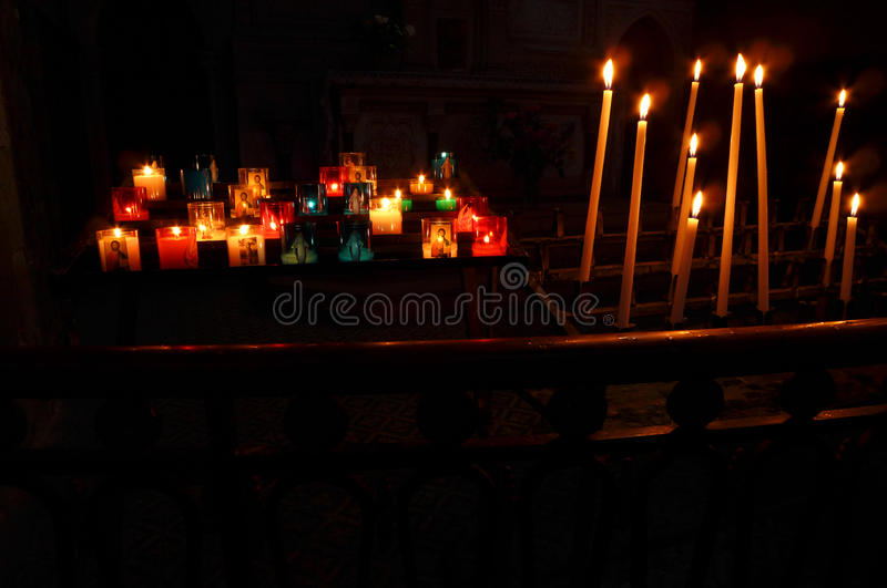 Prayer candles in church. A photograph showing many candles and offering oil lamp lights burning brightly in a dark church backgrorund. Religious offering and stock image
