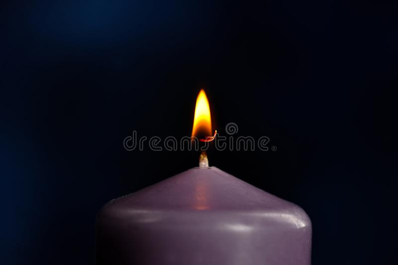 Burning purple candle close-up. On dark background royalty free stock photos