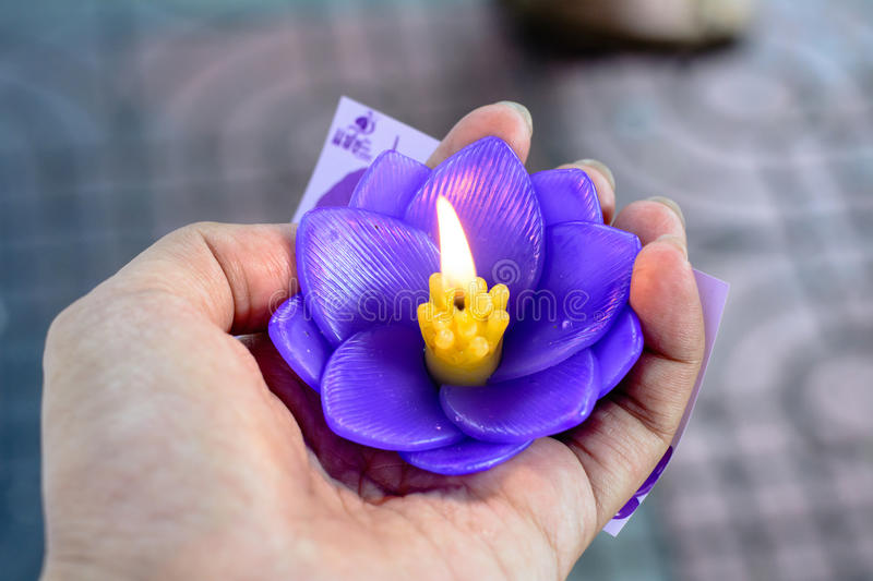 Burning purple candle in shape of lotus flower royalty free stock photography
