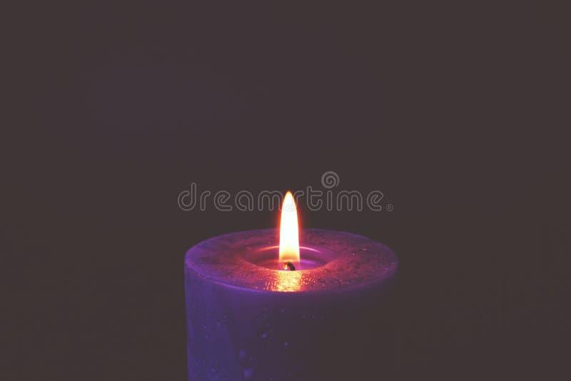 Burning purple candle stock photography