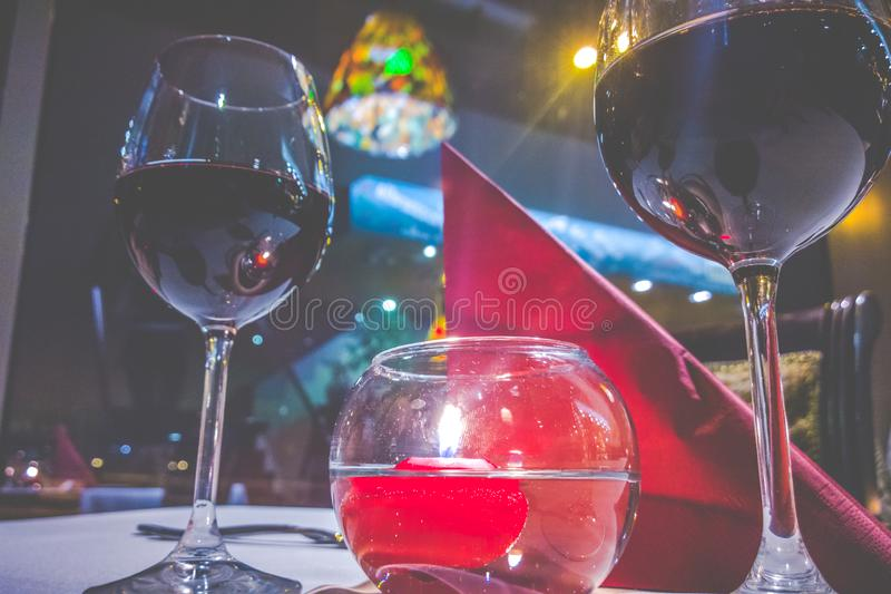 Burning red candle in water and glass of wine royalty free stock photos