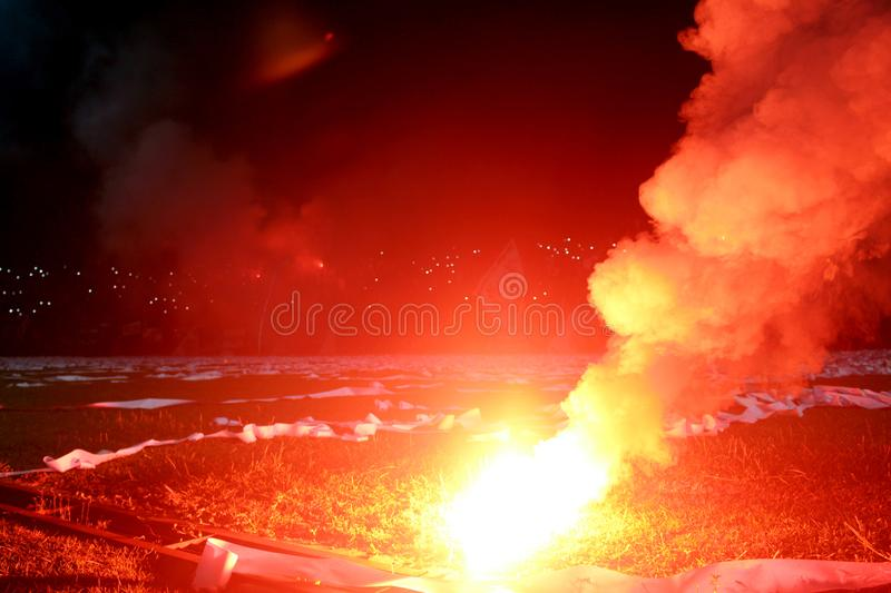 Burning red flare, flame, football hooligan. football fans lit up the lights and smoke bombs on the football pitch. Burning red fl stock images