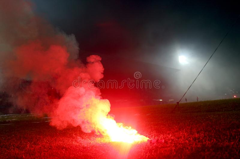 Burning red flare, flame, football hooligan. football fans lit up the lights and smoke bombs on the football pitch. Burning red fl stock photography