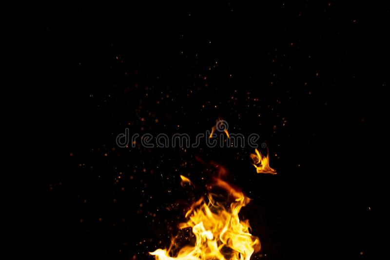 Burning red hot sparks fly from large fire in the night sky. Beautiful abstract background on the theme of fire, light and life. Burning red hot sparks fly from stock images