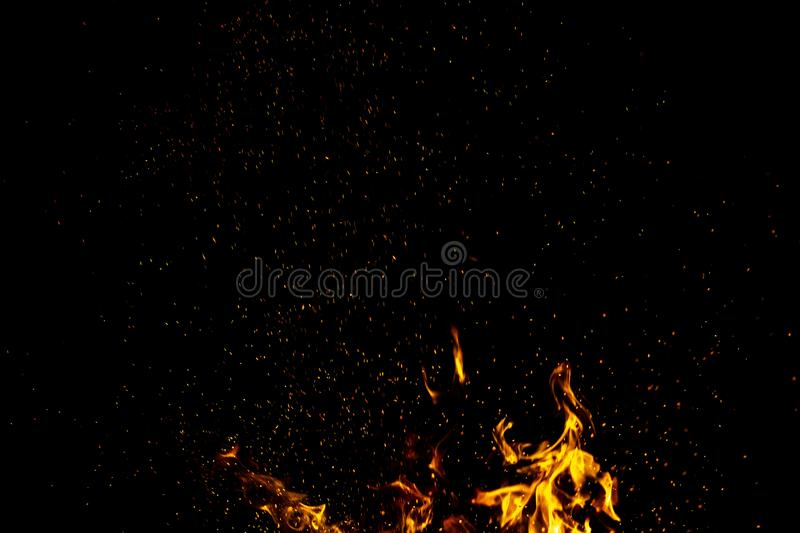 Burning red hot sparks fly from large fire in the night sky. Beautiful abstract background on the theme of fire, light and life. Burning red hot sparks fly from stock photos