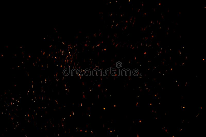 Burning red hot sparks fly from large fire in the night sky. Beautiful abstract background on the theme of fire, light and life. Burning red hot sparks fly from stock image