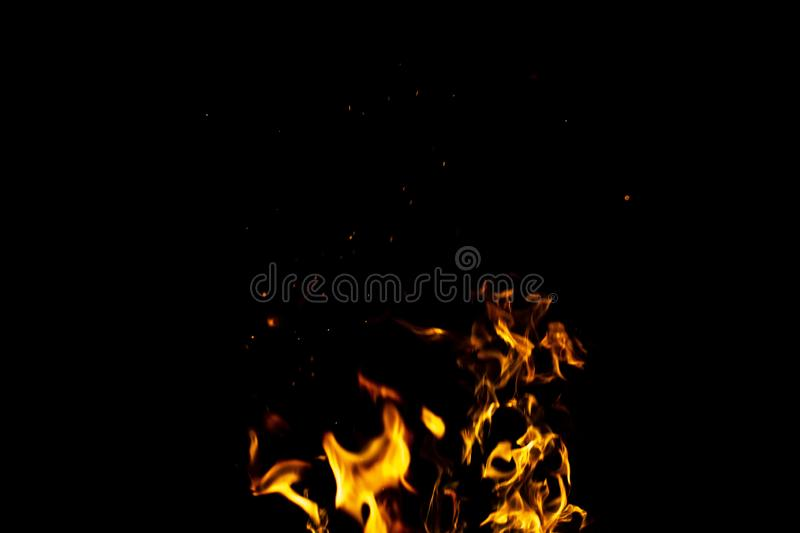 Burning red hot sparks fly from large fire in the night sky. Beautiful abstract background on the theme of fire, light and life. Burning red hot sparks fly from stock photography