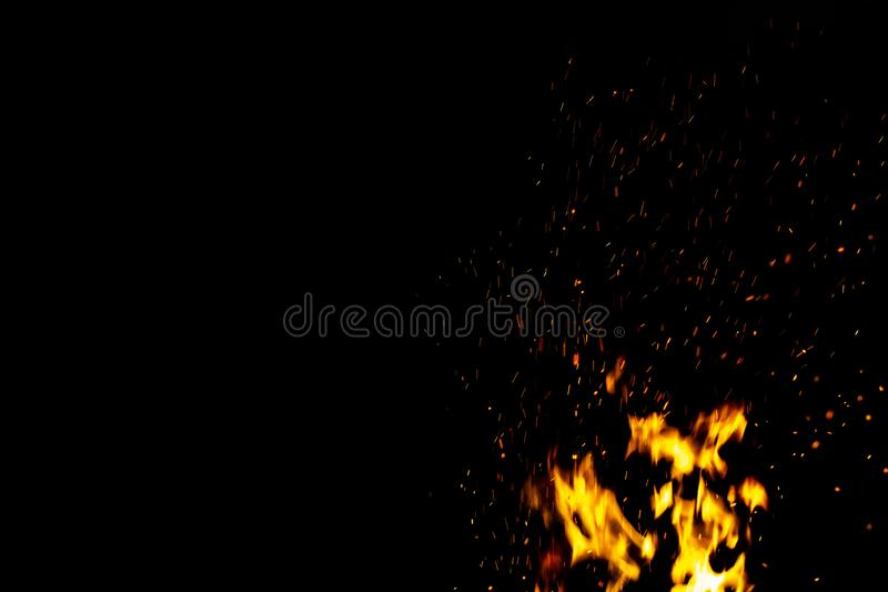 Burning red hot sparks fly from large fire in the night sky. Beautiful abstract background on the theme of fire, light and life. Burning red hot sparks fly from royalty free stock images
