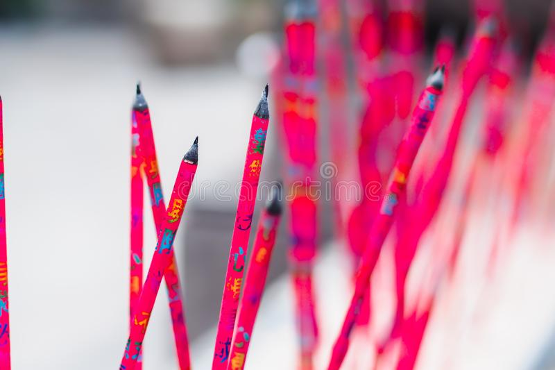Burning red incense sticks in Chinese temple with letter write in the meaning of praying to god and get best luck religion.  stock illustration
