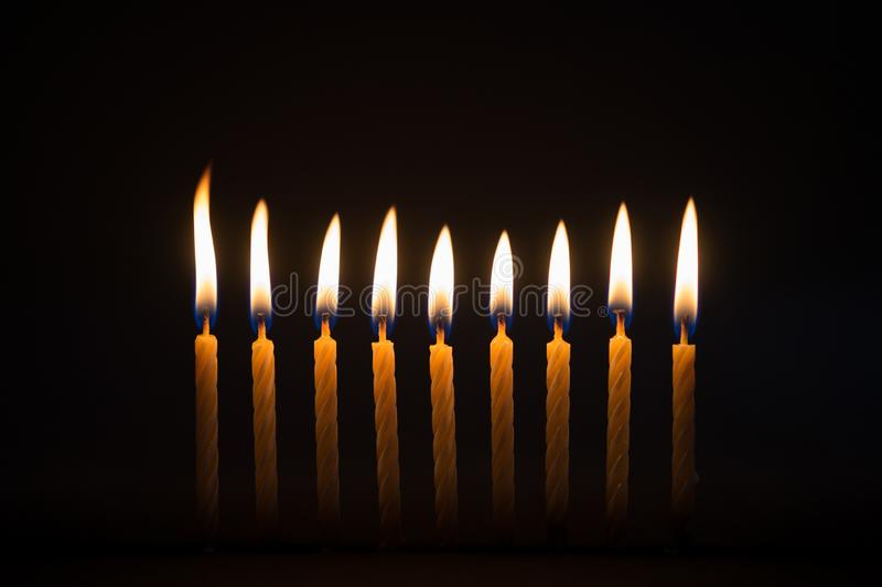 Burning birthday candles with black background. Burning row of birthday candles with dark black background royalty free stock images