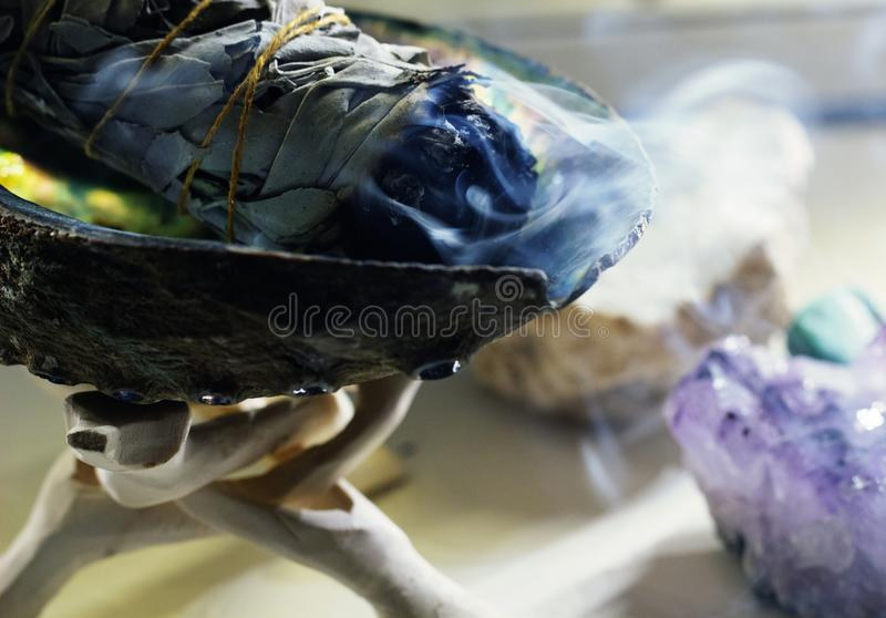 Burning Sage Stick. Health & Wellness Burning sage stick in stand with crystals in the background stock photo