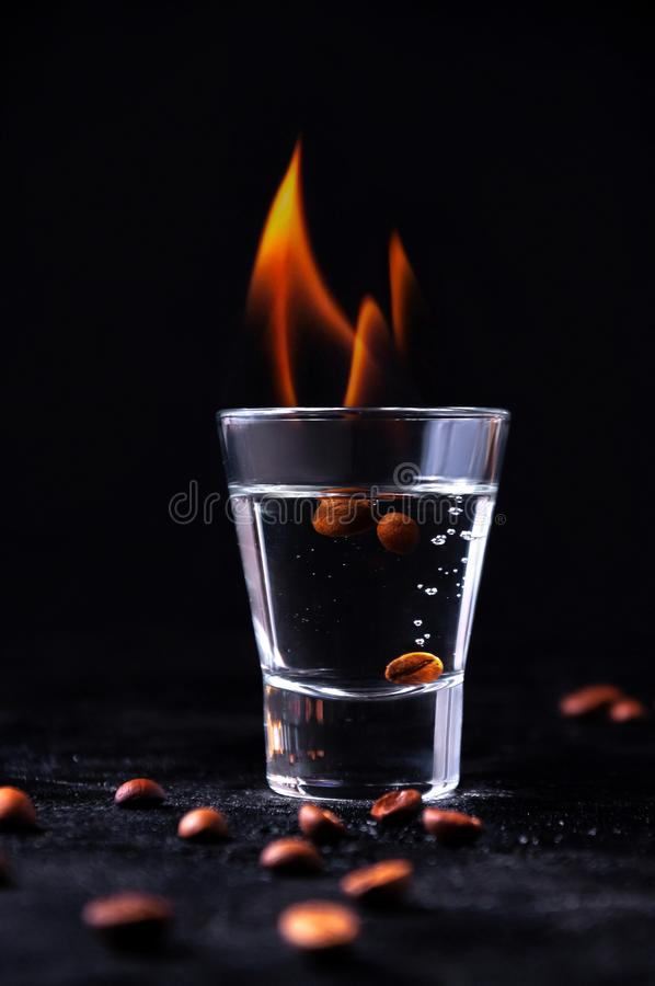 Burning Sambuca in Glass with Coffee Beans on Dark Background. Concept Shot Alcohol Cocktails.  stock images