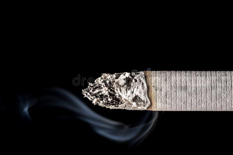 Burning smoldering smoking cigarette close-up with beautiful smoke isolated on black background. royalty free stock image