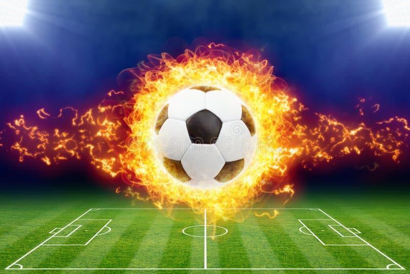 Burning soccer ball above green football stadium stock images