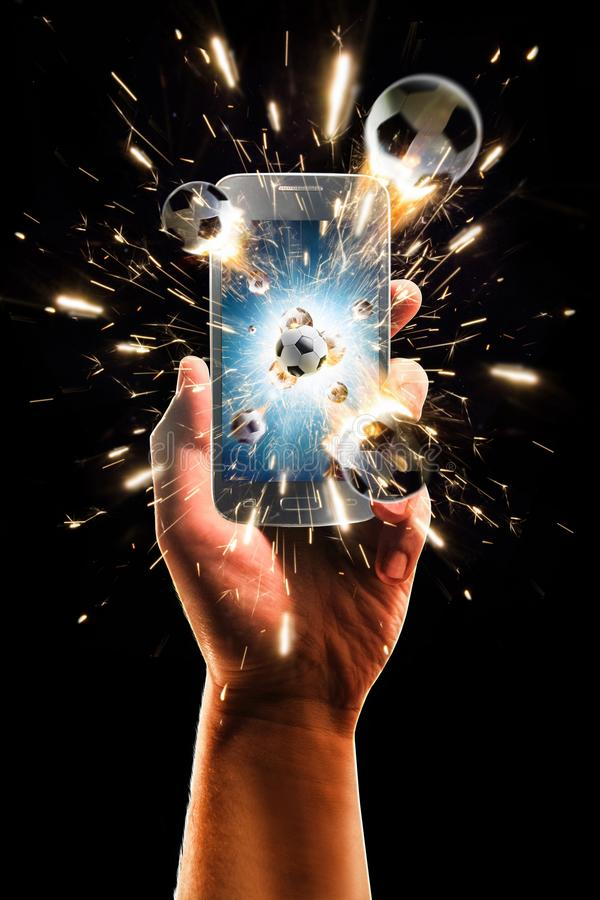 Burning soccer balls flies from the smartphone, black isolated royalty free stock photo