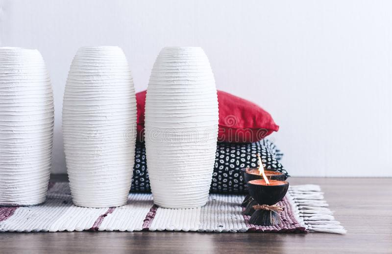 Burning spa aroma candle in coconut shell, decorative pillows and vase on multi-colored rug background, cozy home interior stock photography