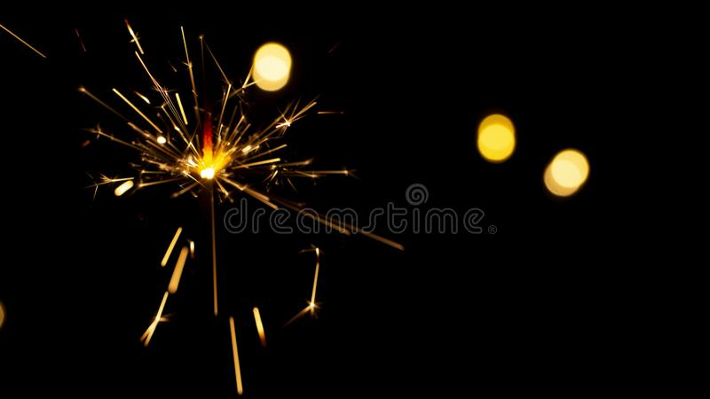 burning sparkler on bokeh background from lights of garland stock photography